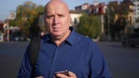 Businessperson Walking op de Straat in Stad de stad in en Tekst die Celtelefoon met behulp van stock videobeelden