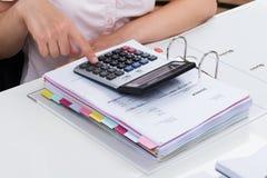 BusinesspersonCalculating Tax With räknemaskin royaltyfri bild