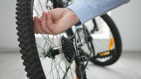 Businesspersonen i cykel shoppar kontrollerar lufttryck från ett gummihjul stock video