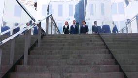 Businesspersons confiados que hablan delante del edificio de oficinas moderno Los hombres de negocios y la empresaria tienen nego metrajes