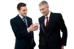 Businesspersons que olha o telefone celular fotografia de stock royalty free