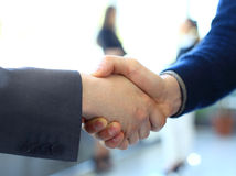 Businesss and office concept - two businessmen shaking hands. In office Stock Photography