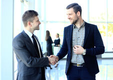 Businesss and office concept - two businessmen shaking hands. In office royalty free stock photos