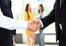 Businesss and office concept - two businessmen shaking hands. In office Royalty Free Stock Photography