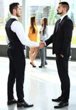 Businesss and office concept - two businessmen shaking hands. In office Royalty Free Stock Image