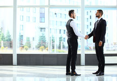 Businesss and office concept - two businessmen shaking hands Royalty Free Stock Photography