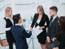 Businesss and office concept - two businessmen shaking hands in Stock Image