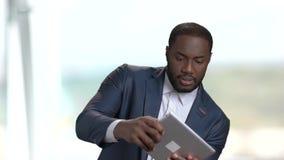 Businesssman afroamericano divertido que juega al juego de ordenador almacen de video