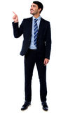 Businesssman looking and pointing upwards Stock Photography