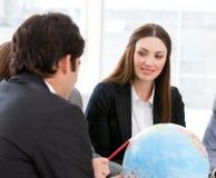 Businessteam смотря земный глобус стоковая фотография rf