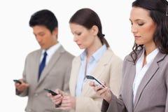 Businessteam смотря их мобильные телефоны стоковые изображения rf