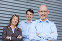 Businessteam With Arms Crossed Against Shutter Stock Images