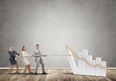 Businessteam, das in der Zusammenarbeit zieht Diagramm mit Seil als Symbol der Macht und der Steuerung arbeitet Lizenzfreies Stockfoto