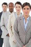 Businessteam di sguardo serio che si leva in piedi insieme Immagini Stock