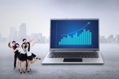 Businessteam en bedrijfsgrafiek op laptop Royalty-vrije Stock Foto's