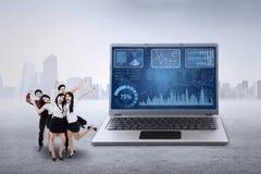 Businessteam et graphique de gestion sur l'ordinateur portable Images stock