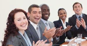 Businessteam feliz que aplaude en una reunión Imagenes de archivo