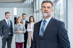 Businessteam i regeringsställning, den lyckliga höga affärsmannen i hans kontor står framme av deras lag arkivfoto