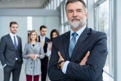 Businessteam i regeringsställning, den lyckliga höga affärsmannen i hans kontor står framme av deras lag royaltyfri foto