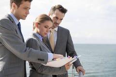 Businessteam mit dem Buch, das auf Terrasse gegen Himmel steht Lizenzfreie Stockfotos