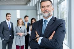 Businessteam in office, Happy Senior Businessman in His Office is standing in front of their team. royalty free stock photo