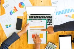 Businessteam with pen and graph in hand are analyzing the work.L Stock Image