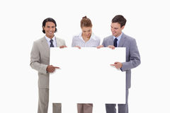 Businessteam pointing at blank sign in their hands Stock Photo