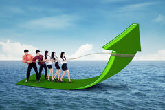 Businessteam pulling arrow upward Stock Photos