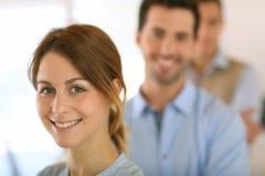 Businessteam que está com a mulher no primeiro plano Fotos de Stock Royalty Free