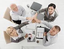Businessteam que levanta las manos juntas en la reunión Fotos de archivo