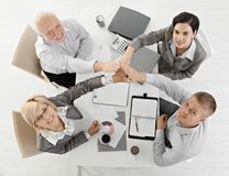 Businessteam raising hands together at meeting. Expressing teamwork, sitting at table, smiling, overhead view Stock Photos