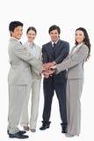 Businessteam sonriente que pone sus manos juntas Imágenes de archivo libres de regalías