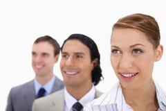 Businessteam sorridente che sta in una fila che sembra giusta Fotografia Stock Libera da Diritti