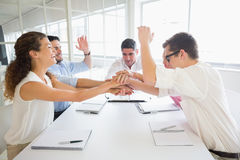 Businessteam stacking hands at table Stock Image
