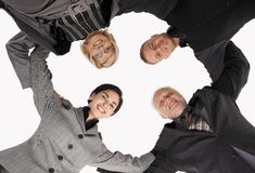 Businessteam standing in huddle, smiling stock images