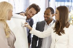Businessteam using whiteboard. Team of young businesspeople working together, using whiteboard, smiling happy Stock Photo