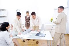Businessteam in work. Five business people working together in office. Three woman and two man. One sitting, one standing, one sitting on desk, one leaning on stock photos