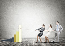 Businessteam working in collaboration pulling graph with rope as symbol of power and control. Young business people pulling up graph bar using rope Royalty Free Stock Image