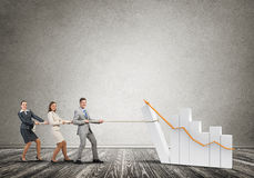 Businessteam working in collaboration pulling graph with rope as symbol of power and control Royalty Free Stock Images