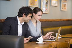 Businessteam working on laptop at coffee bar Stock Photo