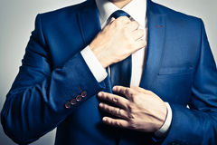 Businesswear. Businessman in blue suit tying the necktie Stock Image