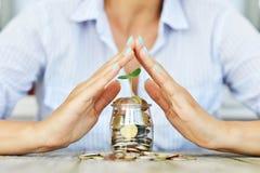 Businesswoman'spalmen die groene installatie het groeien beschermen tegen een kruikhoogtepunt van van van contant geldgeld, bes stock afbeeldingen