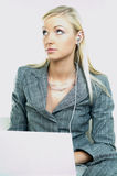 Businesswoman. Portrait of a businesswoman working on laptop computer and listen to music Royalty Free Stock Photo