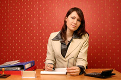 Businesswoman. Young businesswoman doing some paperwork at her desk royalty free stock image