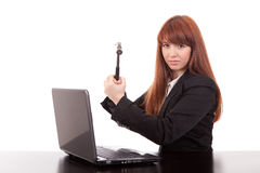 Businesswoman. Fustrated businessman in her office threatening to destroy her PC with a hammer out of sheer frustration Royalty Free Stock Image