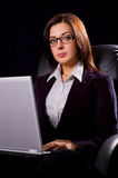 Businesswoman. Beautiful young woman in glasses posing with the laptop on dark background Royalty Free Stock Photos