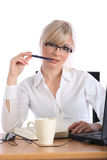 Businesswoman. Attractive blond businesswoman at her office desk holding a pencil near her lips while thinking, isolated on white Stock Image