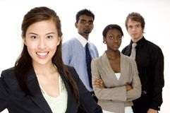 Businesswoman. A smiling asian businesswoman (in focus) stands in front of her team (slightly off focus Stock Image