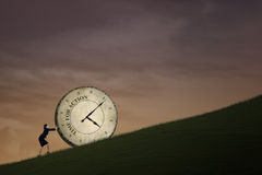 Businesswoman action faster time. Businesswoman is pushing a big time clock on top of a hill. The clock is written Time Royalty Free Stock Images