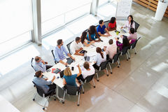 Businesswoman Addressing Meeting Around Boardroom Table Stock Photography